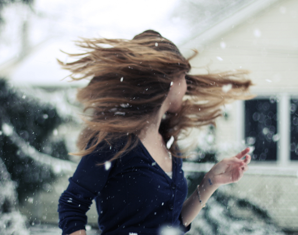 Girl twirling and flipping hair in snowstorm.